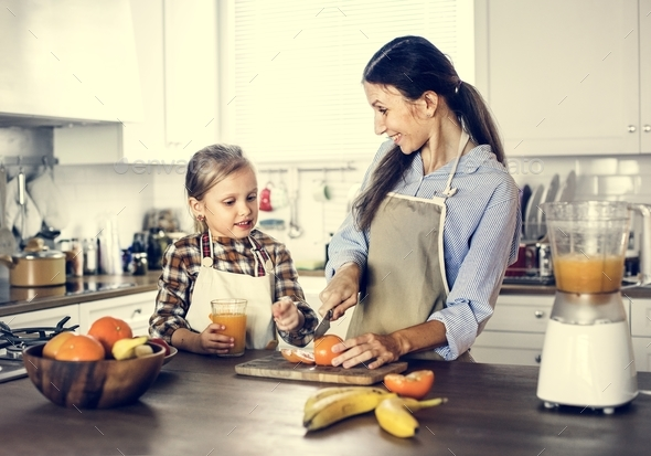 Daughter helping mom in preparing food - Stock Photo - Images