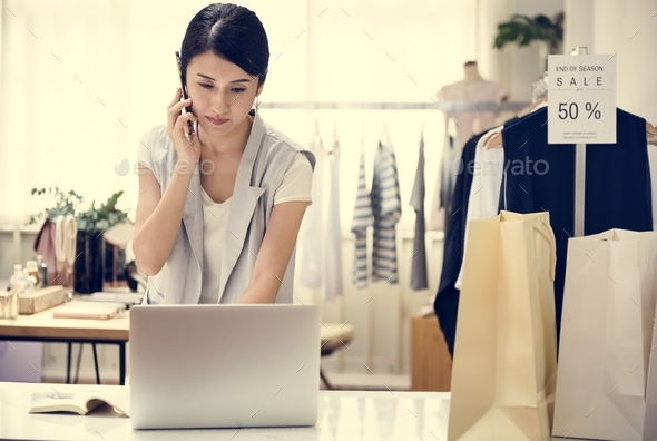 Woman working in a clothing shop - Stock Photo - Images