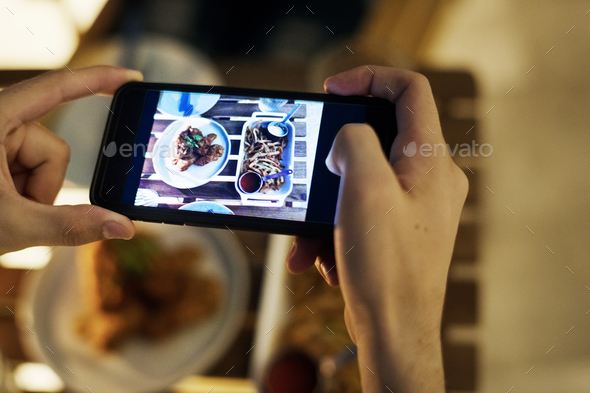 Taking smartphone photo of a dinner plate social media concept - Stock Photo - Images