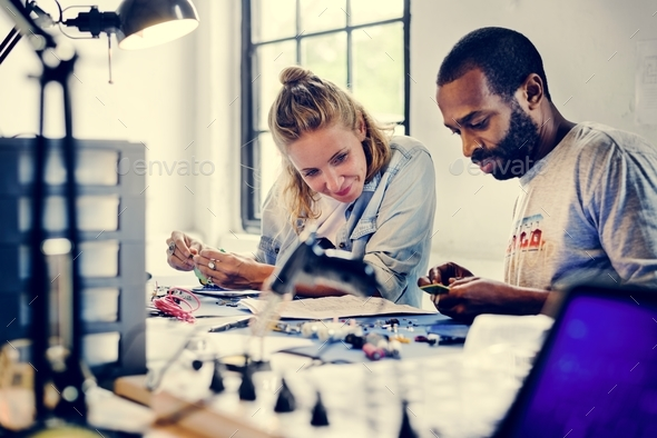 Technicians working on electronics parts - Stock Photo - Images
