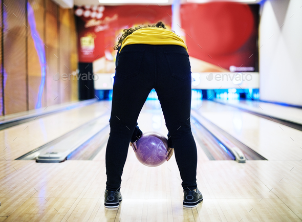 Girl bowling with two hands - Stock Photo - Images