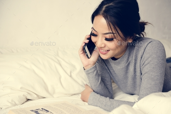 Woman Using Mobile Phone on a Bed - Stock Photo - Images