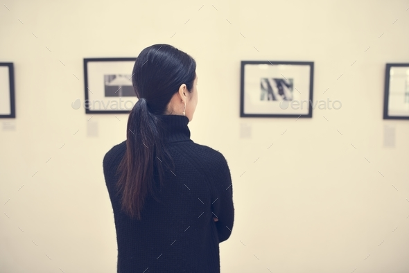 People looking at frames in exhibition - Stock Photo - Images