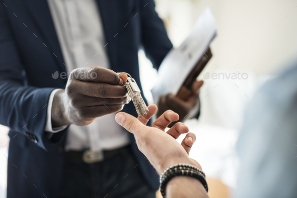 Real estate agent handing the house key to a client - Stock Photo - Images