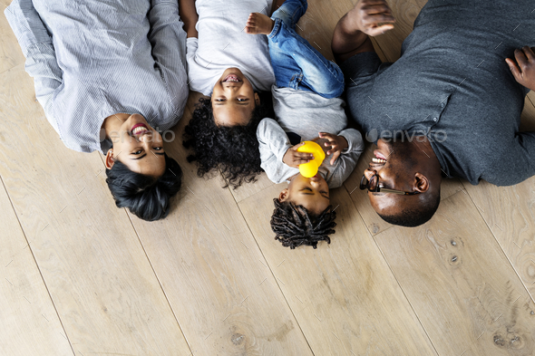 Black family lying on wooden floor design space - Stock Photo - Images