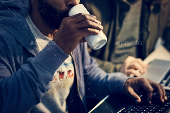 Hacker drinking a can beverage while working - Stock Photo - Images