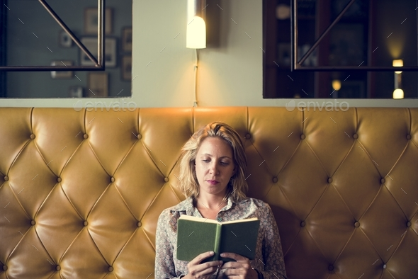 Blond woman reading a book - Stock Photo - Images