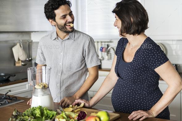 Caucasian couple making fresh smoothie - Stock Photo - Images