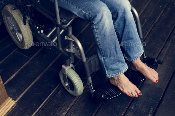 Handicapped woman sitting on a wheelchair - Stock Photo - Images