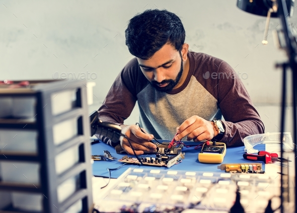 Technician using multimeter with computer electronics parts - Stock Photo - Images