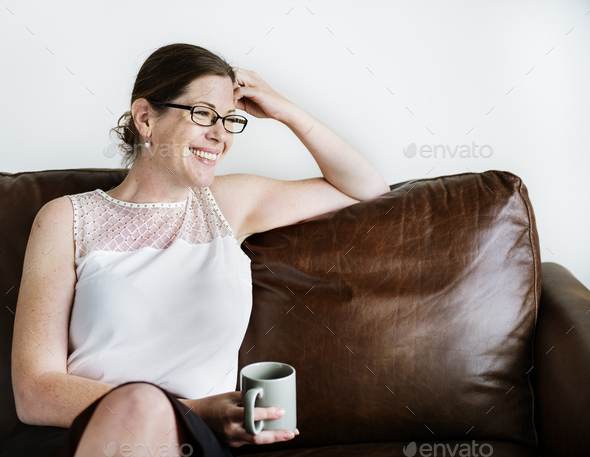 Woman sitting on a couch holding a mug - Stock Photo - Images