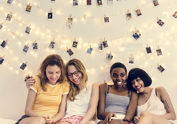 Group of diverse women sitting on bed together - Stock Photo - Images
