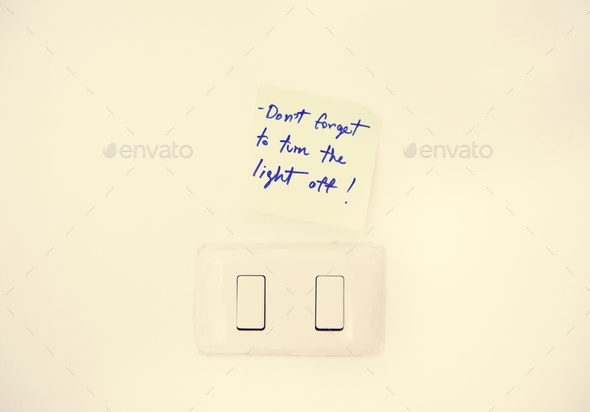 Electric light switch with reminder note on white wall - Stock Photo - Images