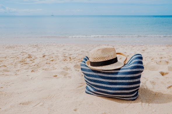 Blue beach bag with hat on the sandy beach with the blue sky background - Stock Photo - Images