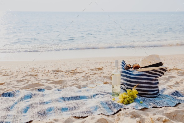 Picnic background with bag, grape and white wine by blue sea - Stock Photo - Images