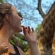 Funny Woman Feed a Giraffe Holding a Peace of Carrot in Her Lips in a Safari Park - VideoHive Item for Sale