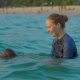Woman Swimming Instructor Teaches Little Boy Swimming in a Sea During a Sundet - VideoHive Item for Sale