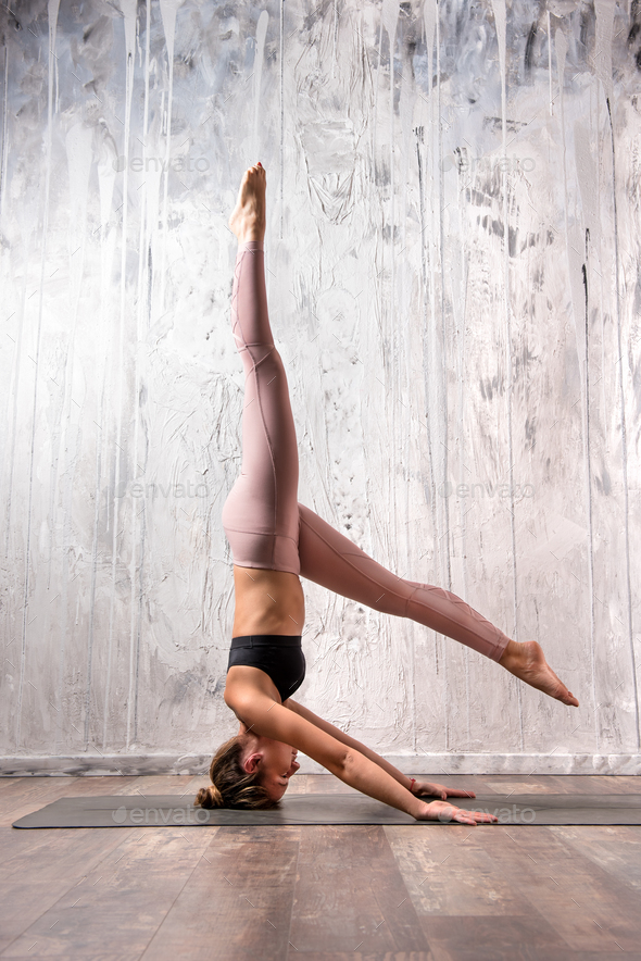 Fit woman doing variation of sirsasana yoga pose - Stock Photo - Images