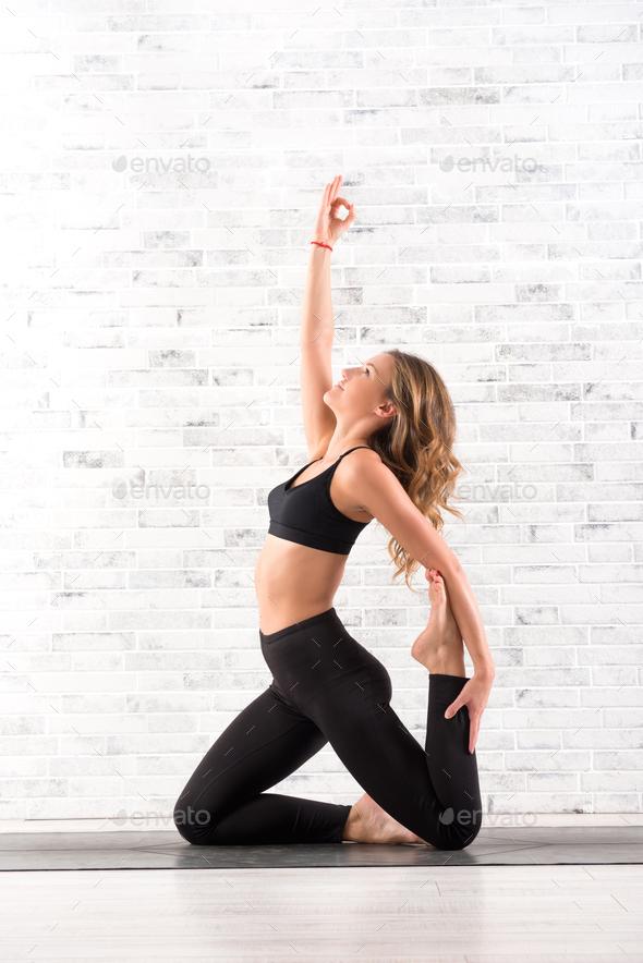 Fit woman doing ardha dhanhrasana yoga pose - Stock Photo - Images