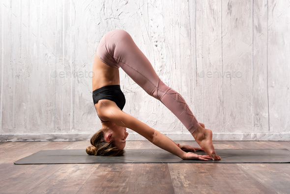 Fit woman exercising sirsasana yoga pose - Stock Photo - Images