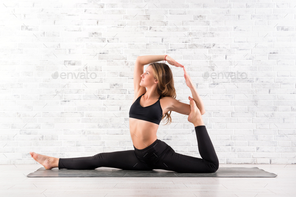 Young fit woman doing yoga pose on mat - Stock Photo - Images