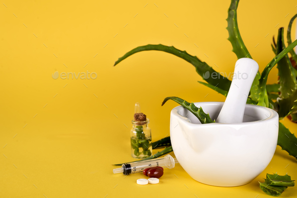 Aloe vera leaf, white mortar full of chopped aloe and bottles of aloe gel or infusion. - Stock Photo - Images