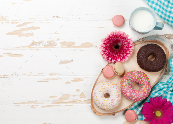 Milk, donuts and flowers on wooden table - Stock Photo - Images