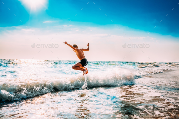 Boy Having Fun And Jumping In Sea Ocean Waves. Jump Accompanied - Stock Photo - Images