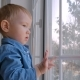 Pensive Little Boy Looking Through Window - VideoHive Item for Sale