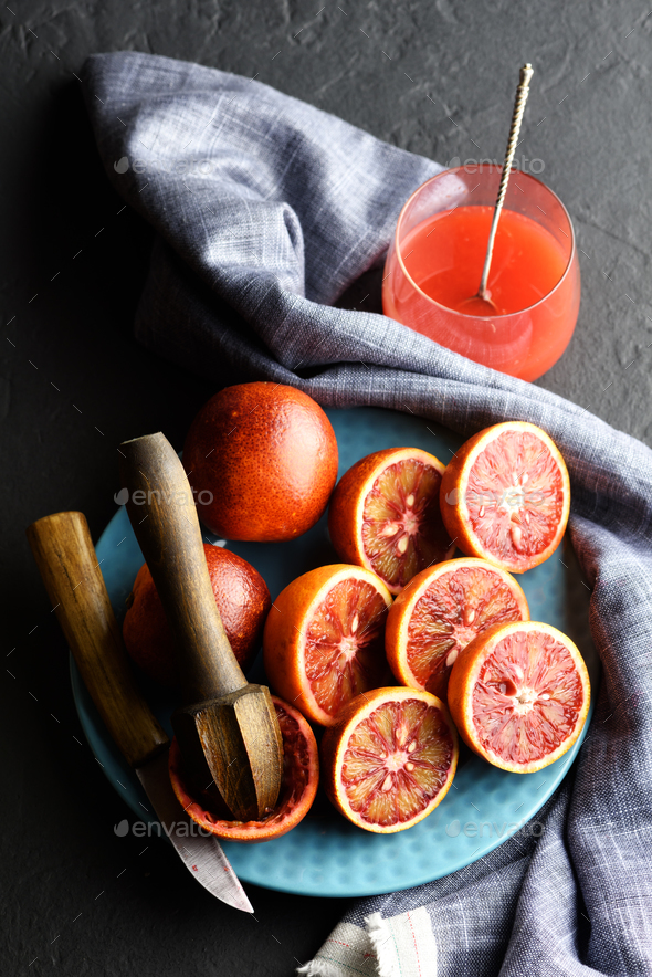 Red sicilian orange pieces on blue plate closeup - Stock Photo - Images