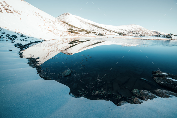 Frozen mountain lake with blue ice - Stock Photo - Images