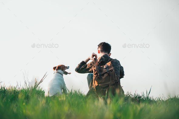 Teenager on green lawn with small white dog - Stock Photo - Images