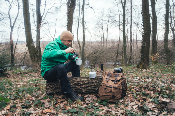 Man with backpack in wild forest - Stock Photo - Images