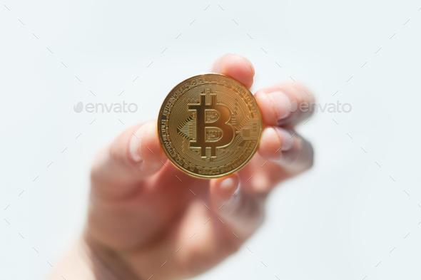 Golden bitcoin coin in man hand closeup - Stock Photo - Images