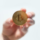 Golden bitcoin coin in man hand closeup - PhotoDune Item for Sale
