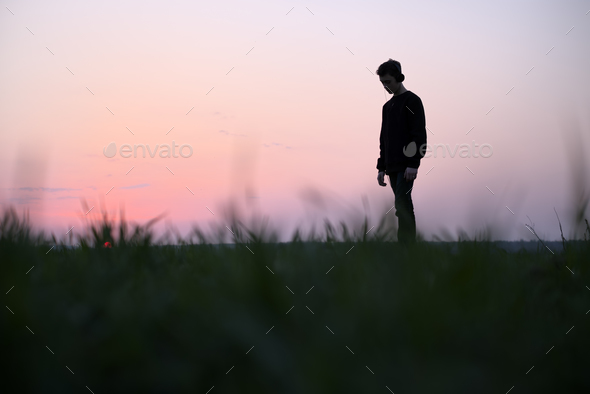 Teenager on green lawn listening music - Stock Photo - Images