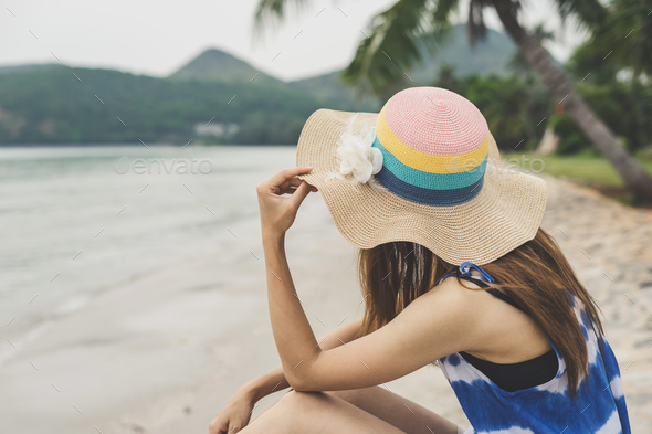 Lonely woman sitting absent minded and looking at the sea - Stock Photo - Images