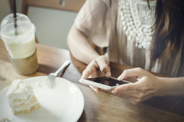 Young woman using smart phone and eating cake in cafe - Stock Photo - Images