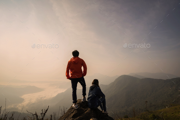 Young couple traveler standing and looking at beautiful landscape on top of mountain - Stock Photo - Images