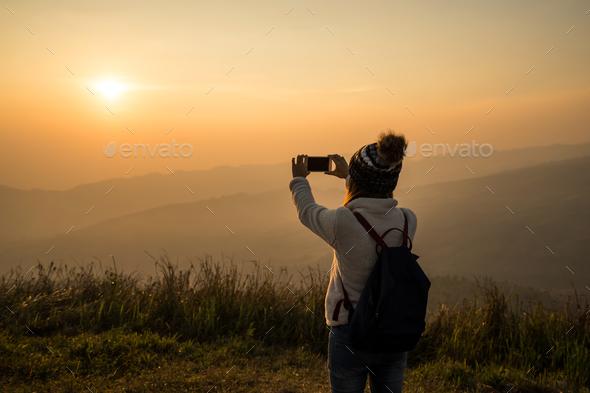 Young traveler taking photo beautiful landscape sunset - Stock Photo - Images