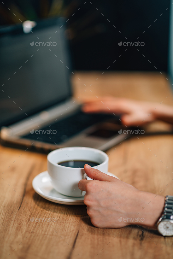 Young woman drinking coffee and working at home - Stock Photo - Images