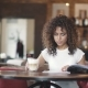 the Girl Looks at the Menu in the Coffee House and Drinks Coffee with Milk. Young Woman Sitting at a - VideoHive Item for Sale