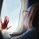 A 6-Year-old Girl with Spectacles Sits in a Plane, Looks Out the Window. Her Hand Is Pressed To the - VideoHive Item for Sale