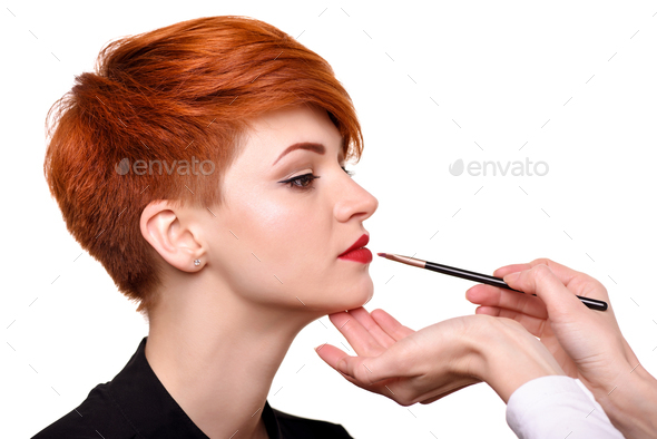 Makeup artist applies lipstick brush on the lips of the model. B - Stock Photo - Images
