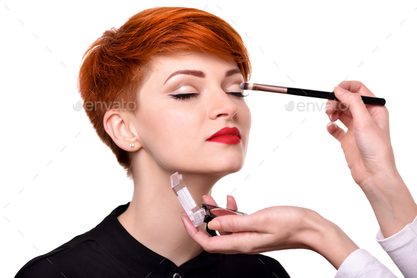 Makeup artist applies eye shadow. Beautiful young woman with sho - Stock Photo - Images