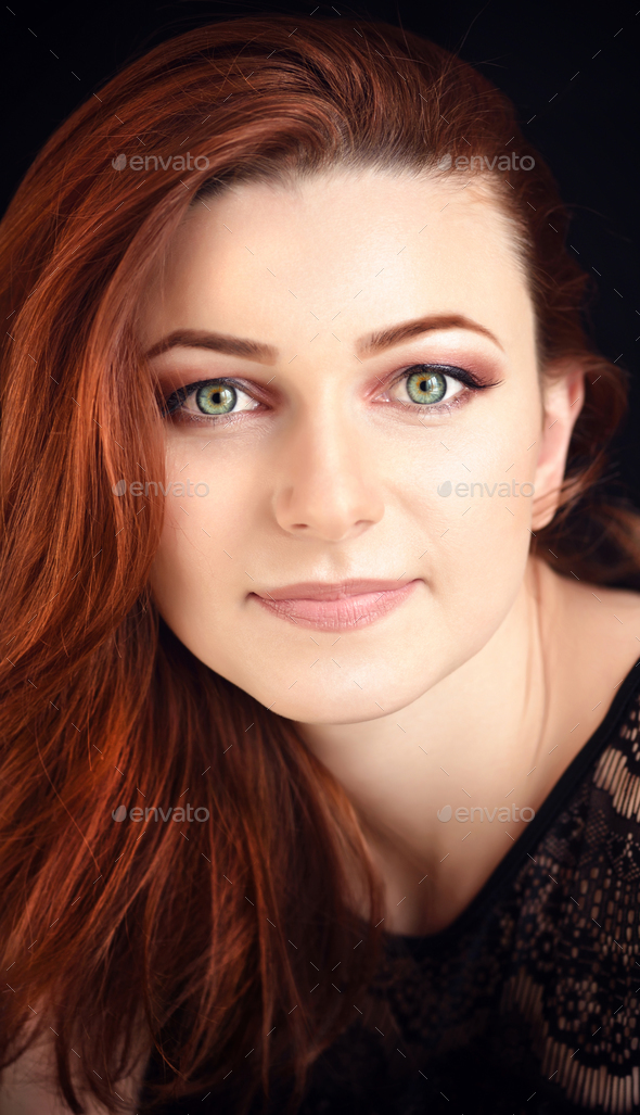 Portrait of a beautiful young woman with long red hair on a dark - Stock Photo - Images
