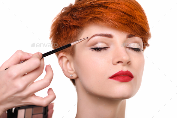 The artist is applying eyeshadow on her eyebrow with brush. The - Stock Photo - Images