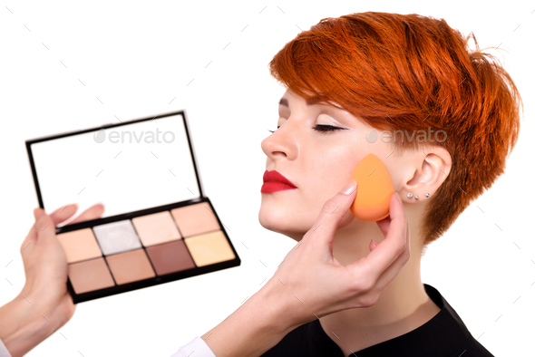 Makeup artist applying foundation on young woman's face using sp - Stock Photo - Images