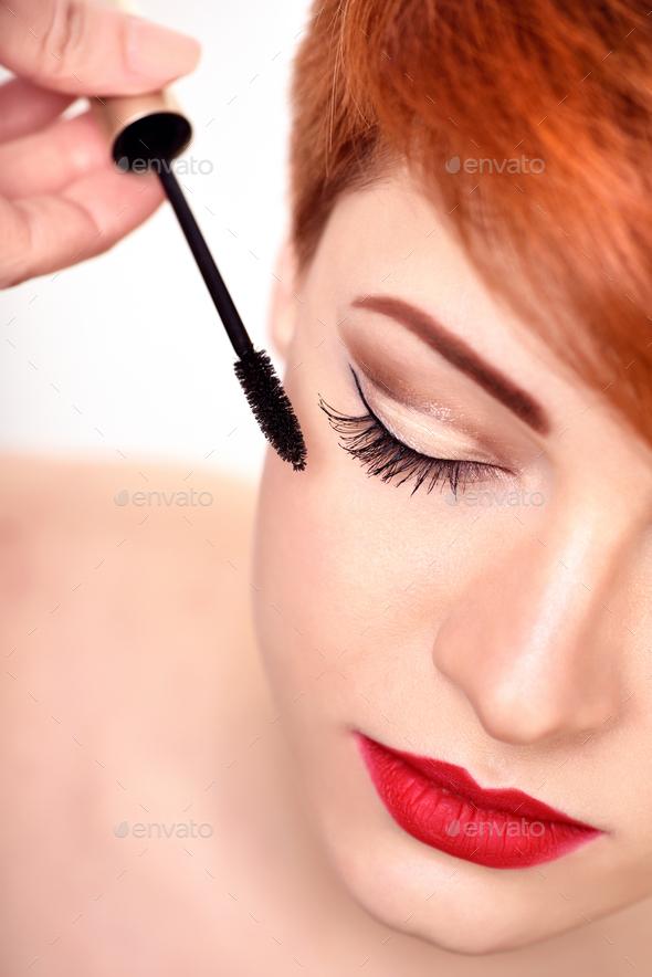 Makeup artist applies mascara brush. Beautiful young woman with - Stock Photo - Images