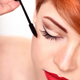 Makeup artist applies mascara brush. Beautiful young woman with - PhotoDune Item for Sale